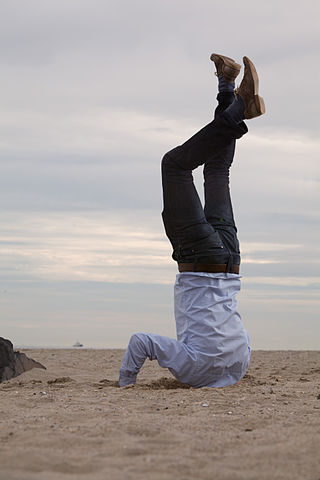Man doing headstand on beach with head buried in the sand