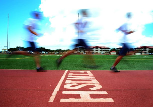 Three strobe-like images of a runner crossing a race track finish line