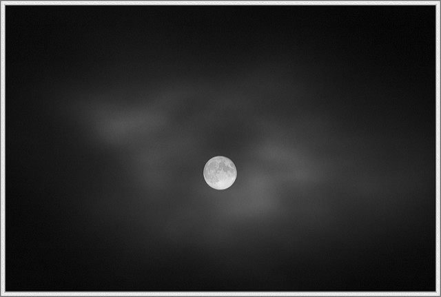Full moon in hazy cloudy night sky