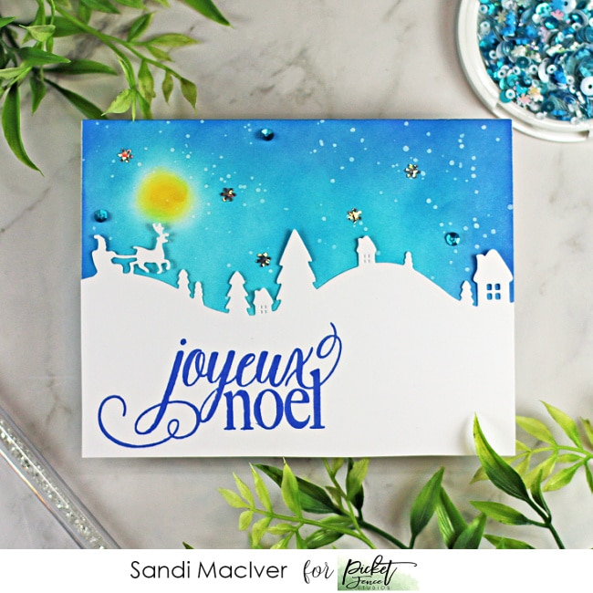 hand made christmas card with a blue sky and full moon and an outline of santa over a vilage created with cardmaking products from Picket Fence Studios