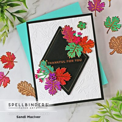 handmade greeting card with fall colored foiled leaves on a white embossed background using card making products from Spellbinders
