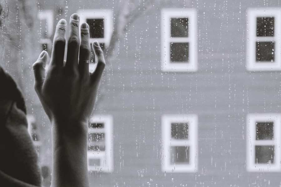 black and white hand on window-moving away from family