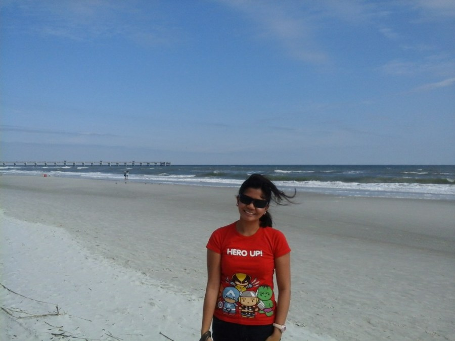 Ruby, a girl in a red t-shirt standing in front of a Florida beach