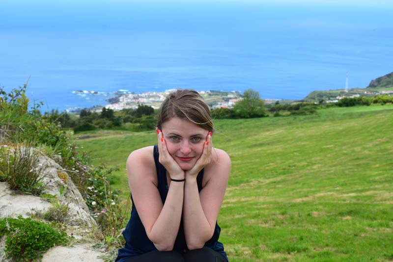 Alexandrina with hands on face with ocean behind her.