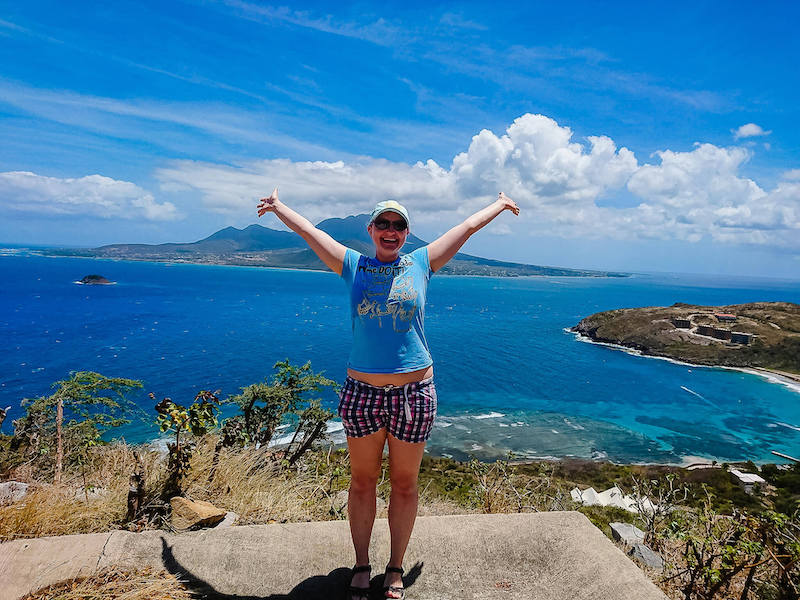 Stephanie with arms outstretched in front of blue ocean and mountains of St Kitts. Reasons to move to another country.