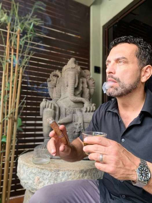 Dark haired man smoking a cigar in front of Ganesh