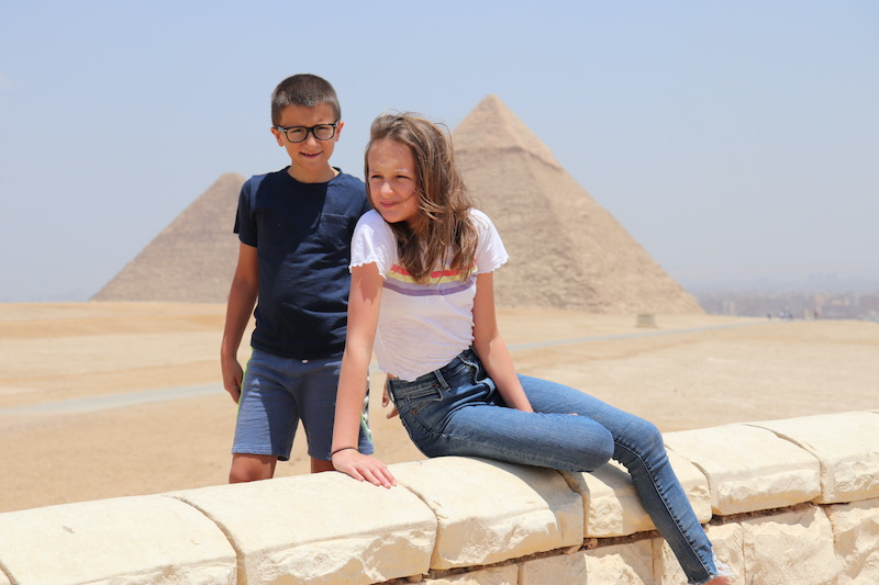 a girl and a boy in front of the pyramids in Egypt