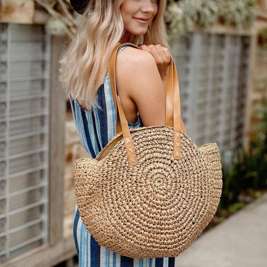 blonde in blue striped dress holding a circular straw beach bag. It makes a great gift for beach lovers