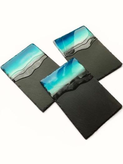 3 black slate serving trays dipped in blue epoxy to make it look like the ocean