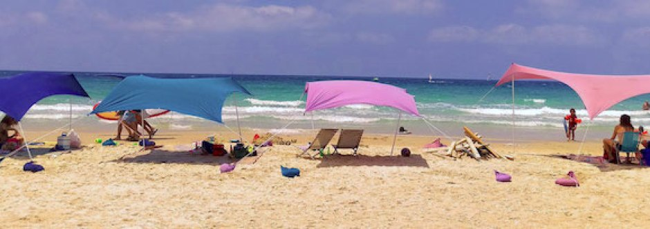 4 different colored beach shades with people sitting under them. Practical gifts for beach lovers