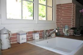 Plan de travail en chêne massif, timbre d'évier blanc, pierres de parement dans les tons rouges et anciens pots en porcelaine.