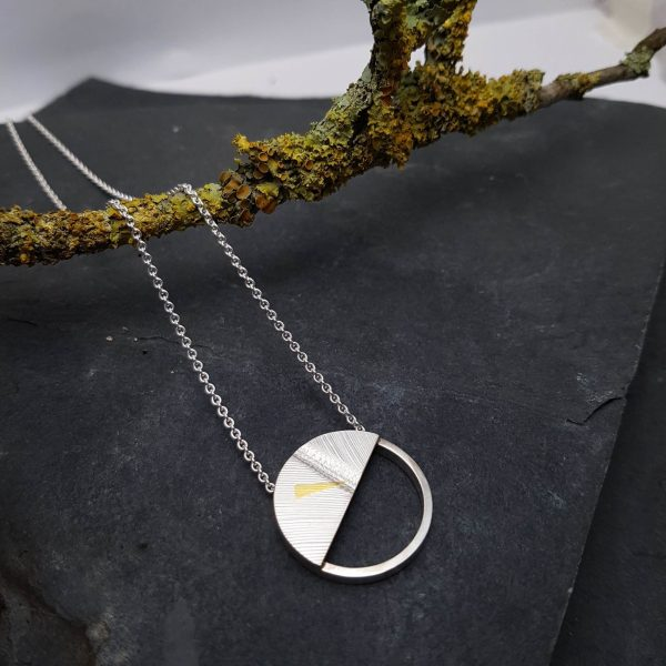 Silver circular pendant with diagonal semi circle section with a feather pattern and dash of 24 carat gold