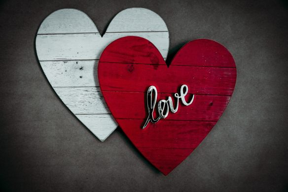 """two wooden hearts, one with the word """"love"""" on it"""