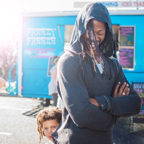 Smiling man in a hoodie with kid behind him looking into camera