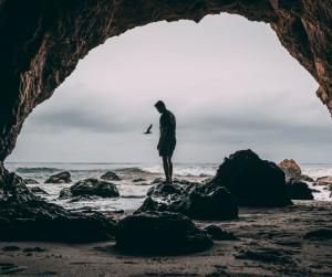 Man standing alone on a rocky beach