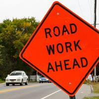 orange road sign - road work ahead