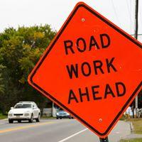 orange road sign - road work ahead