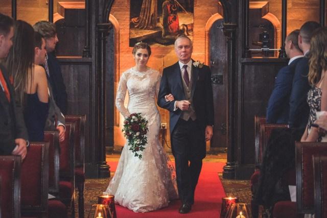 Bride walking down the aisle at Peckforton Castle