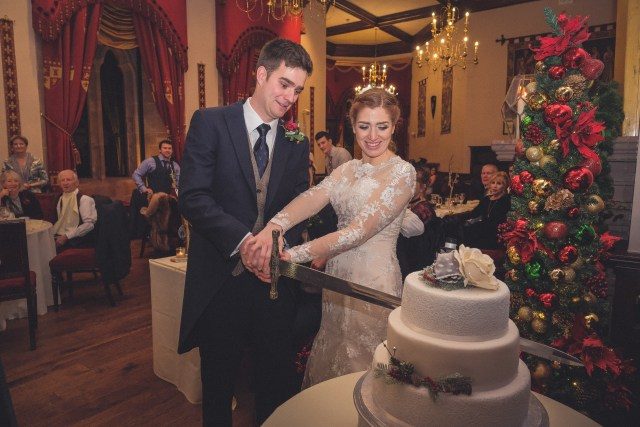 Cutting the cake with a huge sword at Peckforton Castle