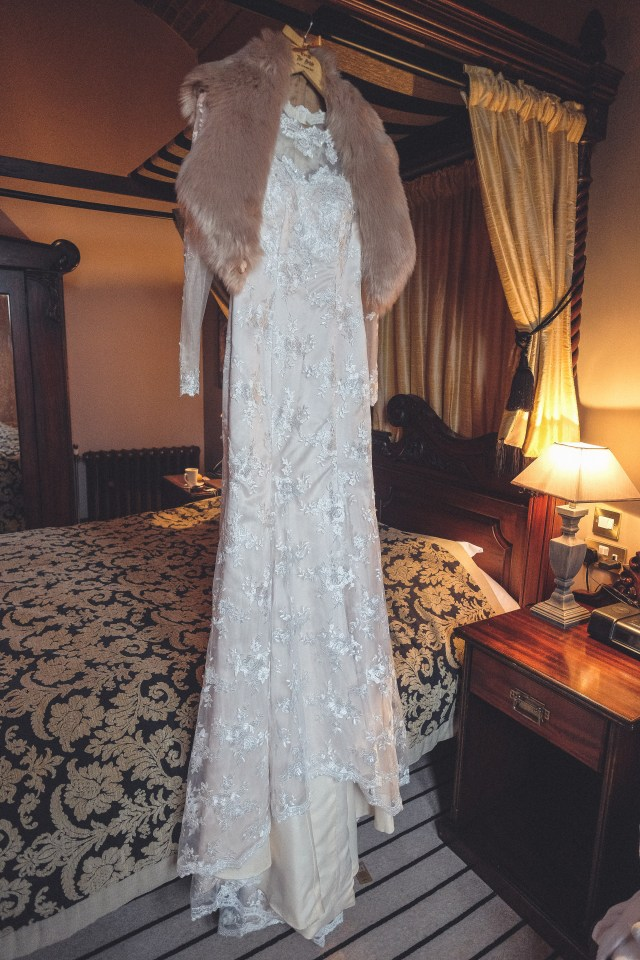 Wedding dress hung from four poster bed