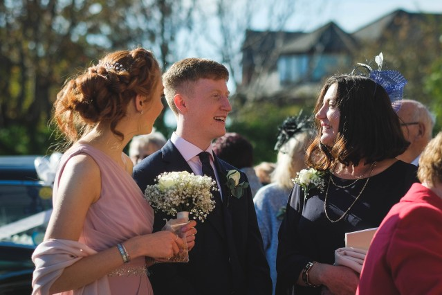 Wedding guests at Wirral church on sunny day