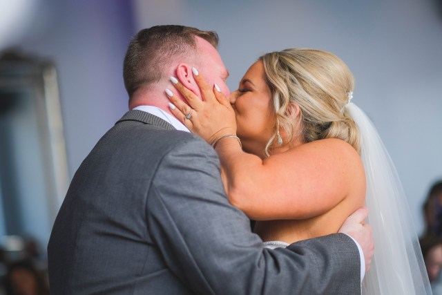 Bride and groom kiss during marriage ceremony