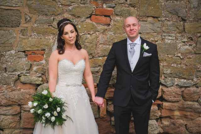 Bride and groom I front of stone wall