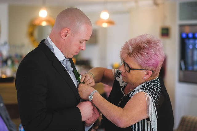 Attaching the groom's buttonhole flowers