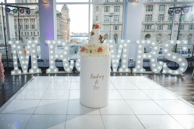 Wedding cake on LED dance floor with view of Liverpool's 3 Graces through the windows