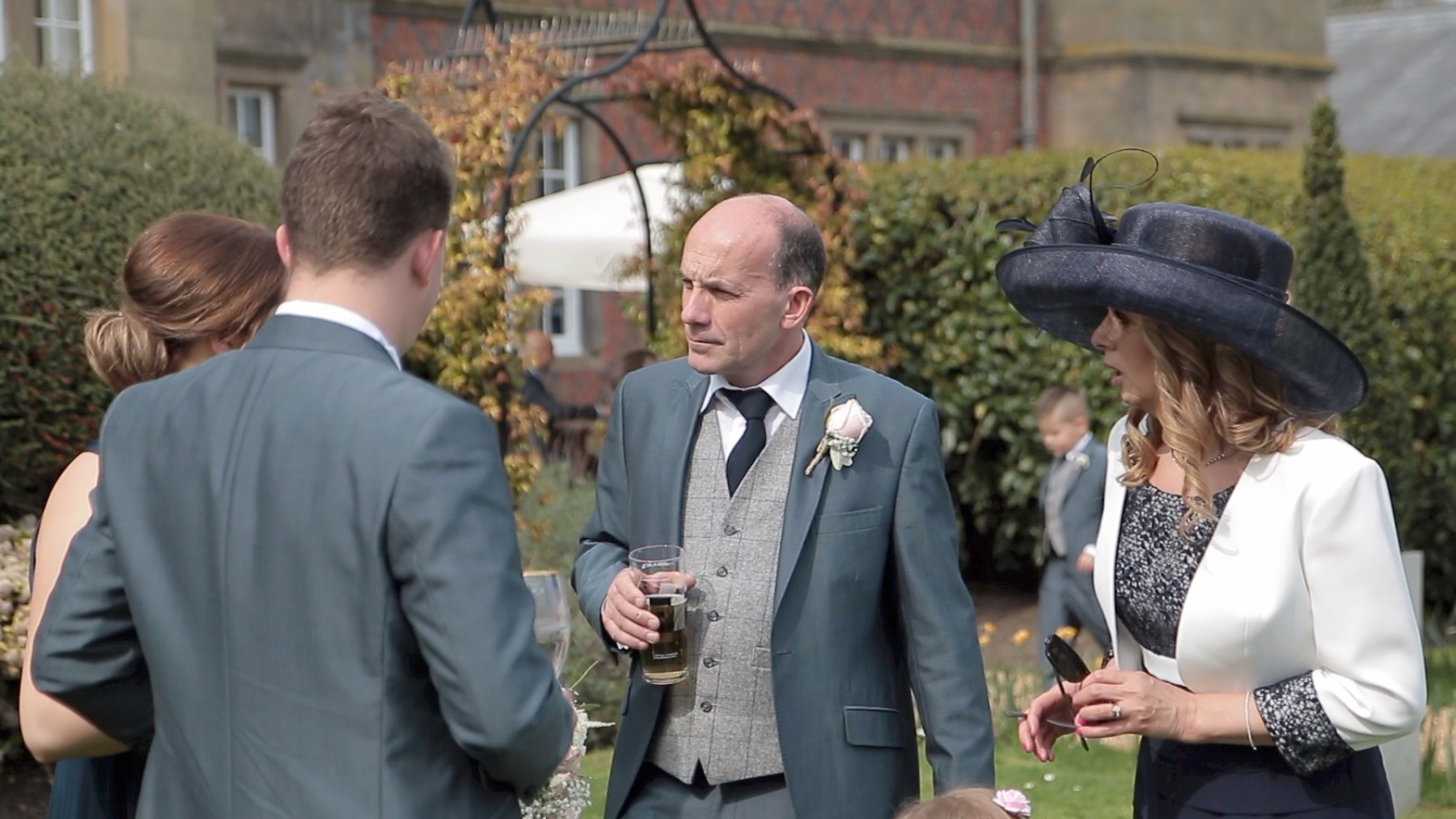 Videographer frame, guests enjoying the sun at Cheshire wedding