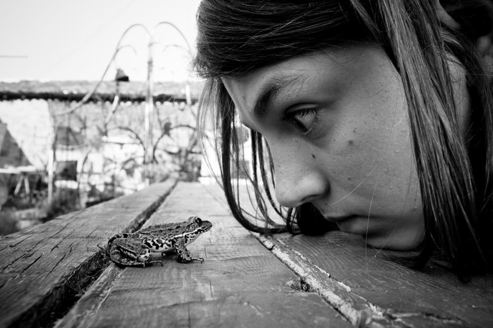 Alain Labels black and white photo of young girl staring at frog
