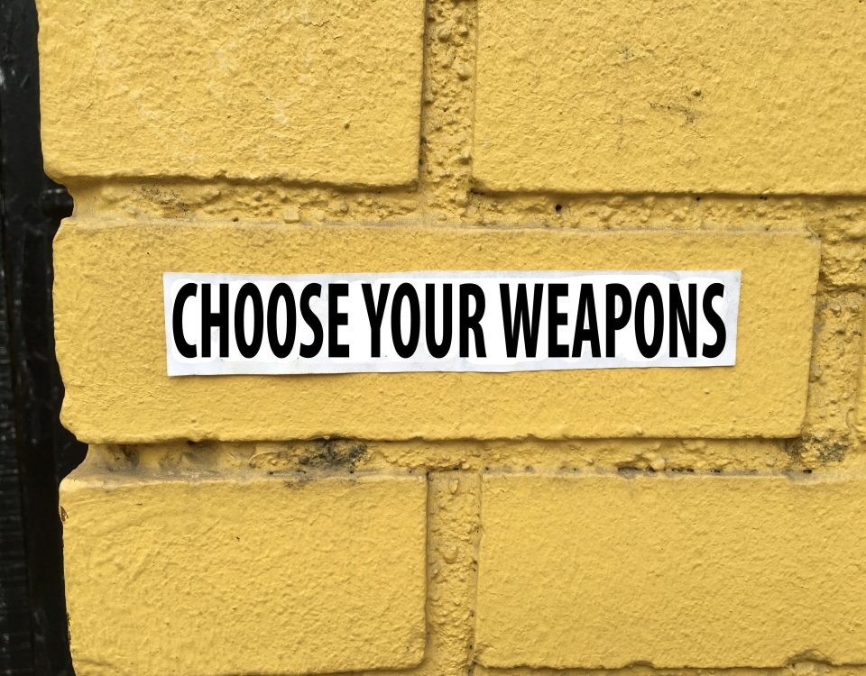 yellow brick wall with text choose your weapons for blog post at sandyhibbardcreative.com