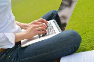 woman with laptop in park/business productivity/sanespaces.com
