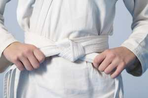 Hands tightening white belt on a teenage dressed in kimono for martial arts, adhd child.