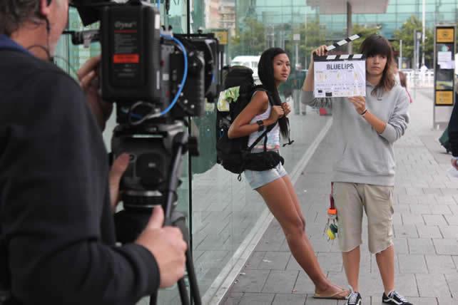 Un momento del rodaje de la película 'Blue Lips', con la actriz esperando con una mochila en la estación de autobuses mientras una integrante del equipo sujeta una claqueta.