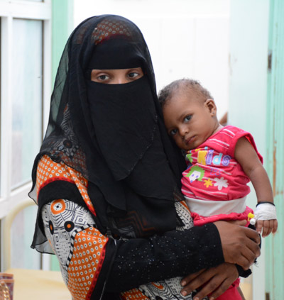 A mother holding her child in MSF supported cholera treatment centre in Al-Sadaqa hospital. The child had cholera and was suffering from acute watery diarrhoea. Image credit: Malak Shaher, MSF