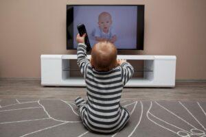 Un bimbo di circa un anno seduto di fronte a un televisore acceso, che trasmette l'immagine di un bimbo coetaneo. Il bimbo è di spalle, indossa una tutina a righe nere e grigie e ha in mano il telecomando