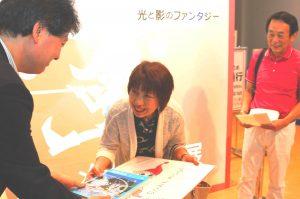 記念品のサイン入り原画を受け取る山本正子さん(中央)