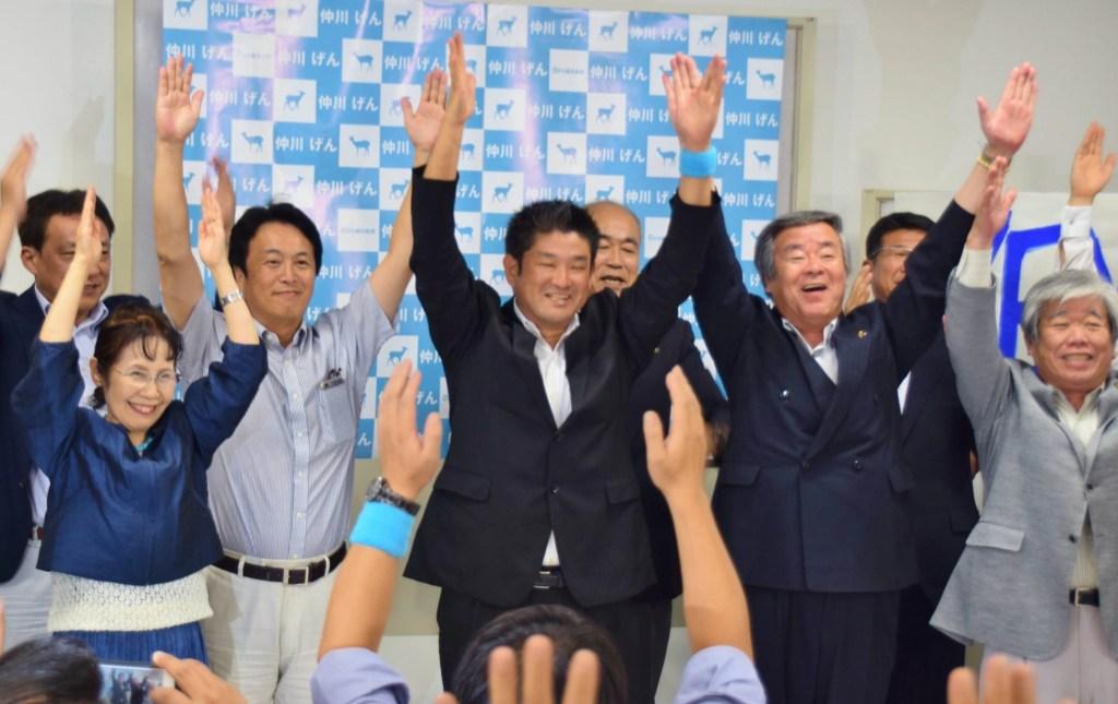 支持者と万歳三唱する仲川げん氏(中央)