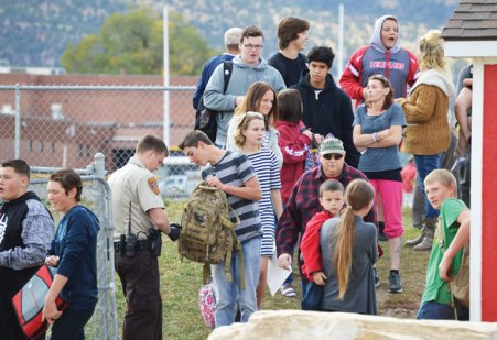 Law enforcement officers search Manti High School students' backpacks before the students boarded buses to go home for the day.