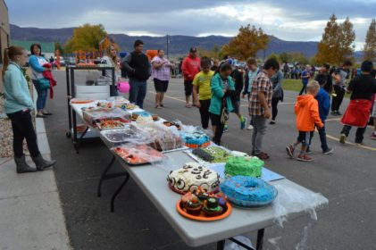 Kids dance around numbers chalked on the ground for a chance to win a decorated item from the calk walk event at the Moroni PTA Fall Carnival. - Daniela Vazquez / Messenger photo