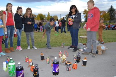 Dante Bailey studies his target carefully before he pitches a winning ring around his prize at the Moroni PTA Fall Carnival. - Daniela Vazquez / Messenger photo