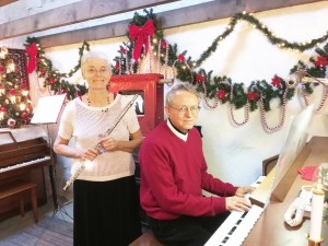 David Rosier and Pat Ellsworth prepare for an nondenominational Christmas Eve candlelight services to be held in the historic Spring City LDS Ward chapel. Rosier will play the organ, while Ellsworth will perform on the flute during the service.
