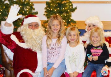 Families stood in a long line that wrapped around the inside of the Greenwood Student Center at Snow  to wait for their turn to sit on Santa's lap. From left to right Haylee, Chelsey and Emma Christensen of Ephraim each took a turn to tell Santa how good they have been this year. - Daniela Vazquez / Messenger photo