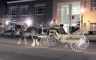 The grand marshals of Manti's Christmas parade, Bill and Carla Mickelson and May Peterson, get a horse drawn carriage ride last Friday. - Tom Osmond / Messenger photo