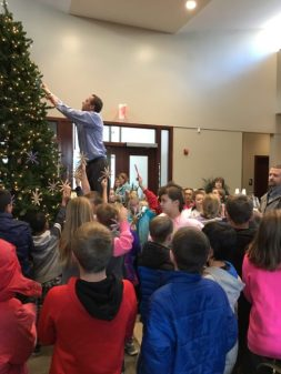 Ephraim Elementary students watch as Zions Bank Ephraim branch manager Nate Christensen climbs a latter to hang kids' hand-crafted ornaments high on the 20-foot tree that stands in the lobby.