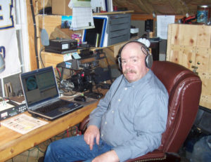 """Spencer Shields of Hideaway Valley, a member of  the Skyline Amateur Radio Club and one of the instructors for the club's  upcoming amateur radio licensing class, is seen here in his """"radio shack"""" along with his radios."""