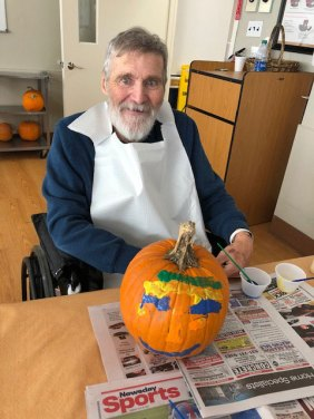 Resident decorating a pumpkin for Halloween