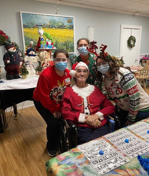 3 San Simeon staff members and a resident in Christmas attire