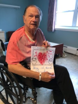Male San Simeon resident holding up Valentine's Day card